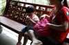Little girl takes her medicine, Traditional Chinese Medicine shop, Hu Qing Yu Tang, Hangzhou