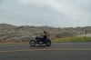 Biker passing Yellow Mounds Overlook, Badlands SD