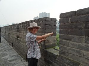Thea pointing west to the Silk Road from the ancient city wall of Xi'an